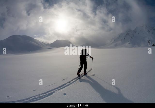 Esquiador de travesía glaciar cruza bajo el cielo tormentoso tarde en el día. Imagen De Stock