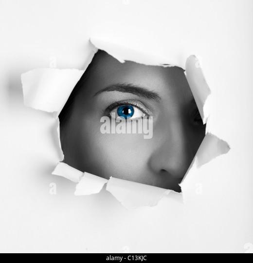 Hermosa hembra blue eye mirando a través de un orificio en una hoja de papel. Imagen De Stock
