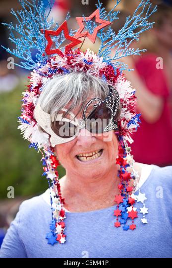 Una mujer vestida con traje patriótico se encuentra en la I'En Comunidad desfile del 4 de julio. Imagen De Stock