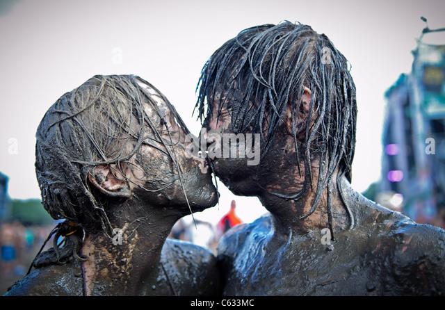 Joven pareja besándose cubierto de barro en el Przystanek Woodstock - al aire libre más grande de Europa Imagen De Stock