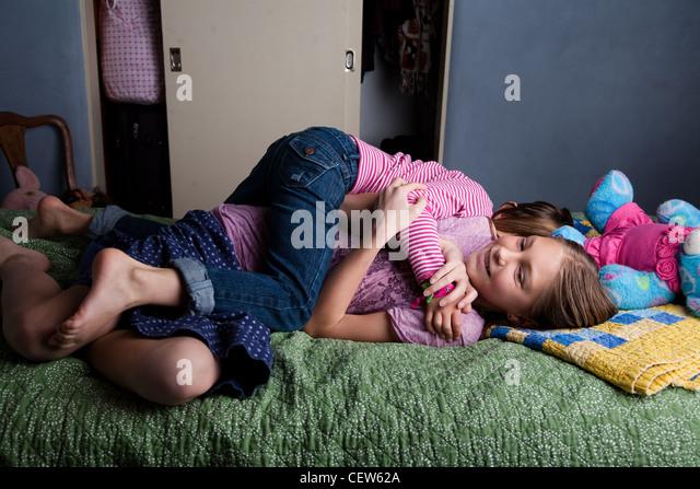 Dos niñas luchando sobre la cama Imagen De Stock