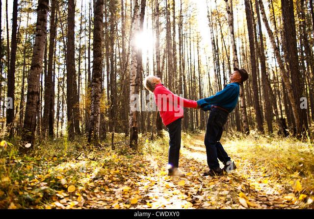 Una feliz pareja de jubilados reír y sonreír durante una caminata a través de un bosque durante el Imagen De Stock