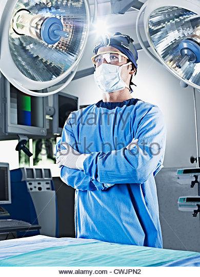Retrato del cirujano serio con los brazos cruzados bajo luces quirúrgicas Imagen De Stock