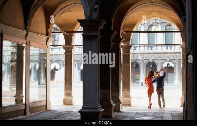 Pareja de bailarines en arco en Venecia. Imagen De Stock