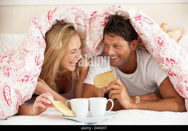 Pareja acurrucada bajo el edredón desayunando Imagen De Stock