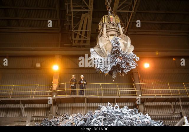 Los trabajadores siderúrgicos viendo pinza mecánica en fundición de acero Imagen De Stock