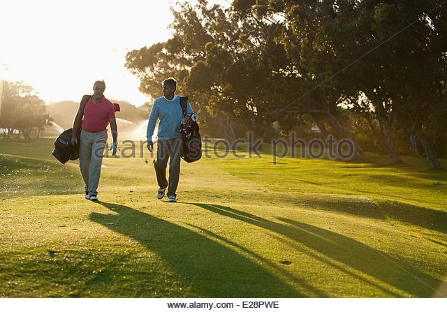 Hombres que llevaban bolsas de golf el campo de golf Imagen De Stock
