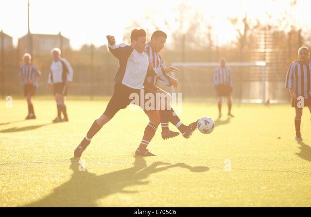 Los jugadores luchan por la pelota de fútbol Imagen De Stock