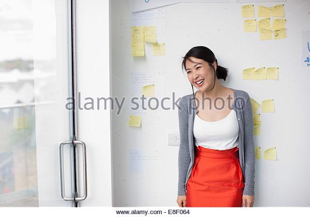 La empresaria sonriendo con delante de pizarra con notas adhesivas Imagen De Stock