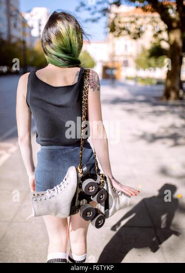 España, Gijón, vista posterior del joven con el pelo teñido de verde llevando patines en línea Imagen De Stock