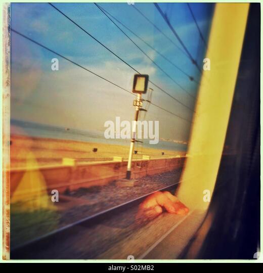La reflexión de la mano de un joven mirando por la ventana del tren en la costa norte de Barcelona, Cataluña, Imagen De Stock