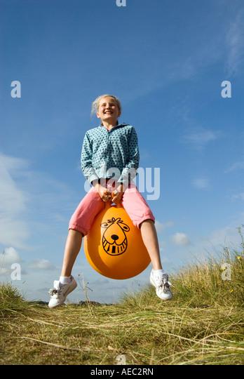 Jeune fille de rebondir sur un Space Hopper, England UK Photo Stock