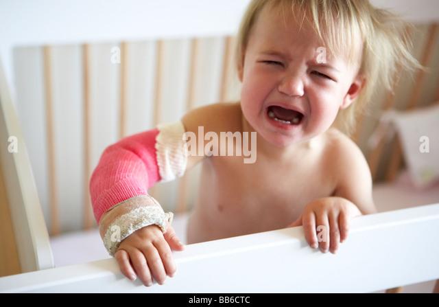Pleurer tout-petit avec le bras dans le plâtre Photo Stock