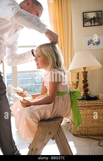 Père prépare les cheveux de la fille Photo Stock