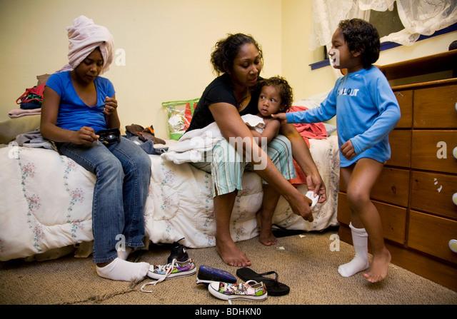 Selena Pina, un sans-abri, mère de quatre enfants s'habiller pour l'école à la famille Centre Photo Stock