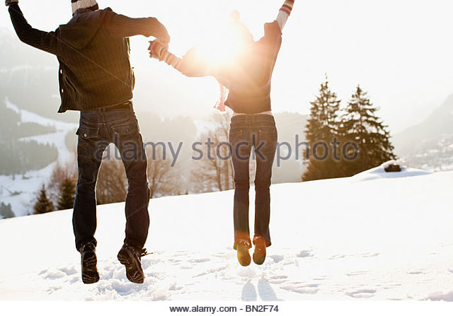 Couple jumping outdoors in snow Photo Stock