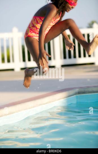African American girl de sauter dans une piscine. Photo Stock