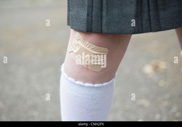 Le genou d'écolière avec un sparadrap sur une coupe. Photo Stock