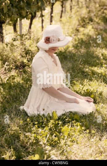 Une femme dans une robe victorienne blanche assise sur l'herbe entre les vignes Photo Stock