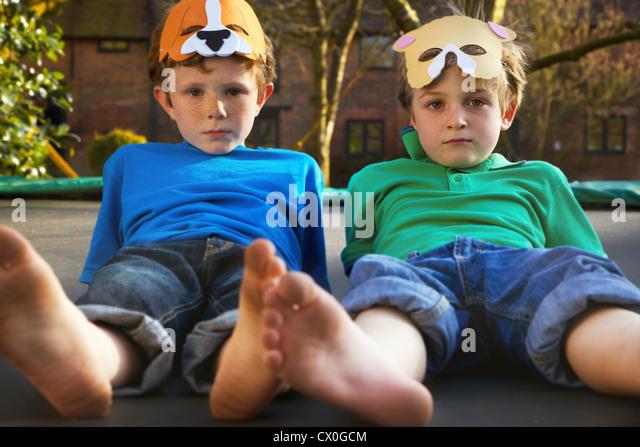 Deux garçons portant des masques allongé sur trampoline Photo Stock