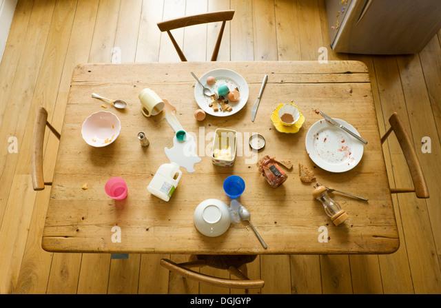 Vue de dessus de table de petit déjeuner avec des aliments consommés et les plaques en désordre Photo Stock