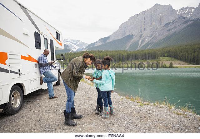 Family standing at lakeside près de RV Photo Stock