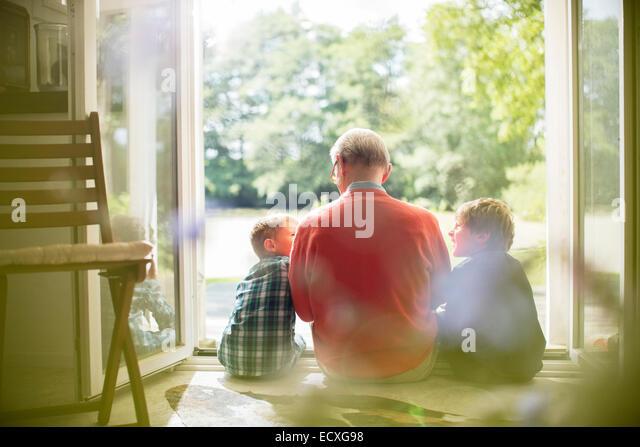 Grand-père et ses petits-fils assis dans la porte Photo Stock