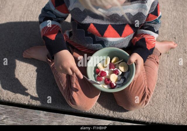 Boy holding bol de fruits, high angle Photo Stock