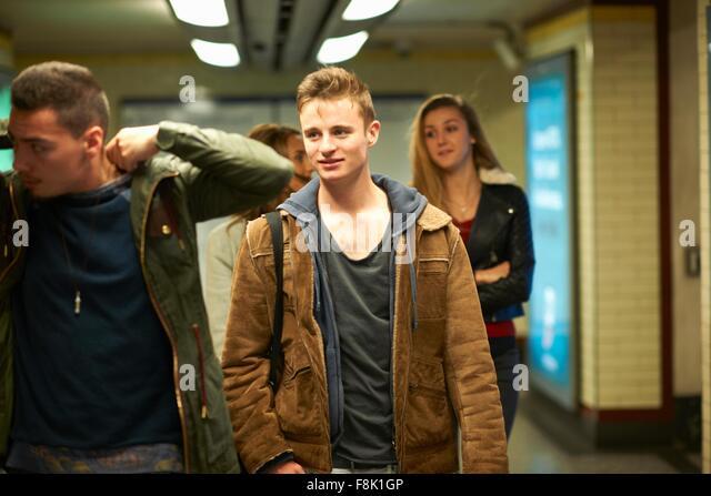 Quatre jeunes amis adultes marche à travers la station de métro de Londres, London, UK Photo Stock