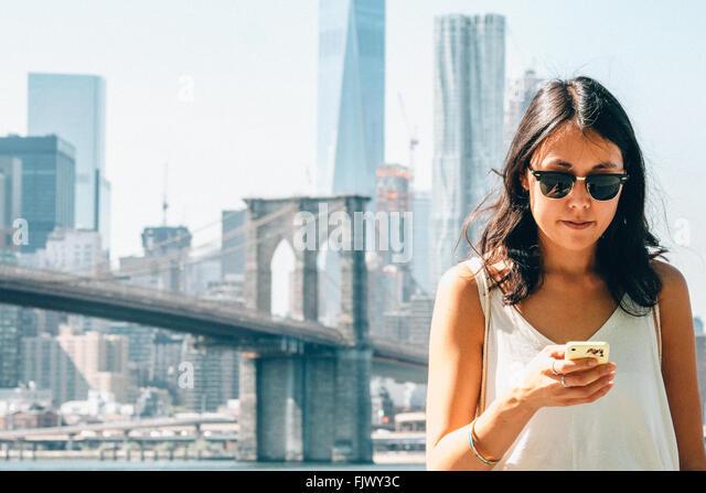 Young Woman Using Smart Phone contre Pont de Brooklyn Photo Stock