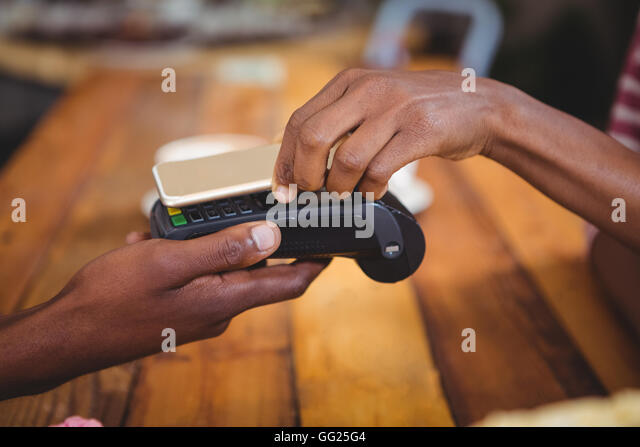 Femme de payer bill par smartphone à l'aide de la technologie NFC Photo Stock