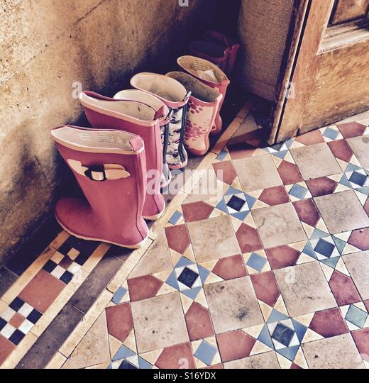 Une famille de bottes la queue à la porte Photo Stock