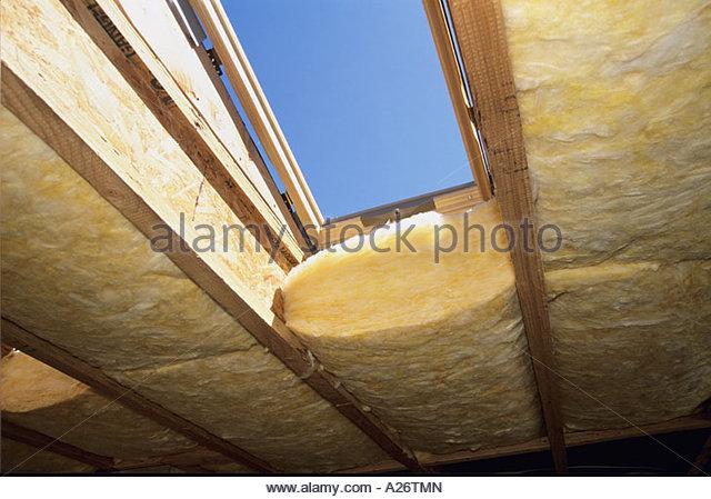 R38 isolamento in fibra di vetro che viene installato nel tetto nuovo stile loft home in costruzione Immagini Stock