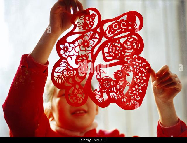 Un Cinese 9 10 anno vecchia ragazza incollando una finestra carta tagliata sul cinese capodanno Immagini Stock