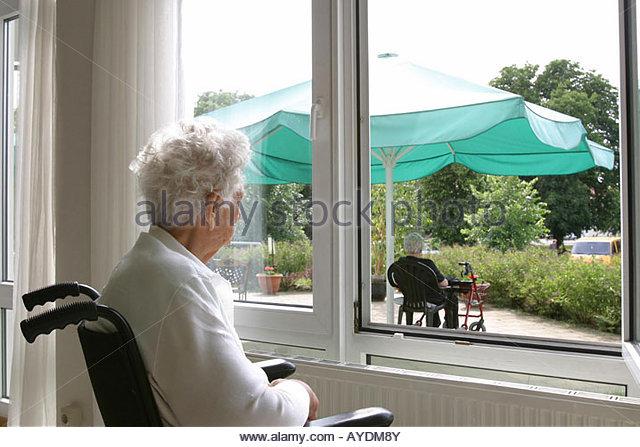Vecchia donna su una sedia a rotelle di guardare attraverso una finestra Immagini Stock