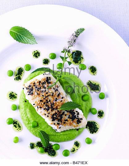 Filetto di pesce con sesamo su purea di piselli e vinaigrette di lime Immagini Stock