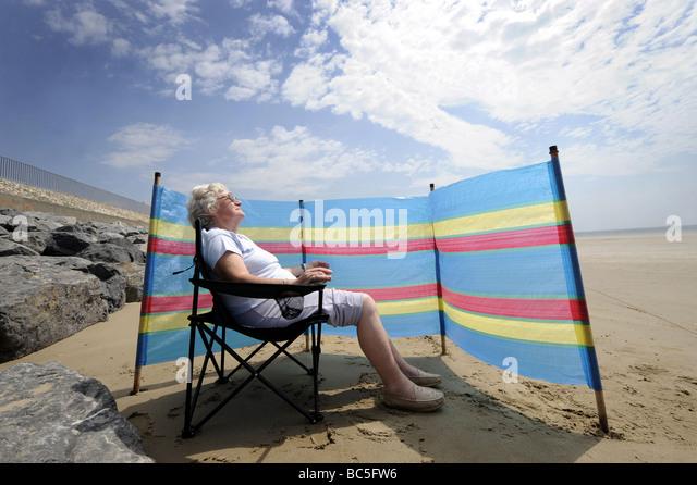 Una vecchiaia pensionato gode di prendere il sole su una spiaggia britannico con la giacca a vento ri vacanze Pensione Immagini Stock