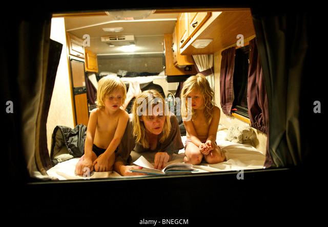 Madre la lettura di una storia prima di addormentarsi per i suoi figli in un camper RV in Texas, Stati Uniti d'America Immagini Stock