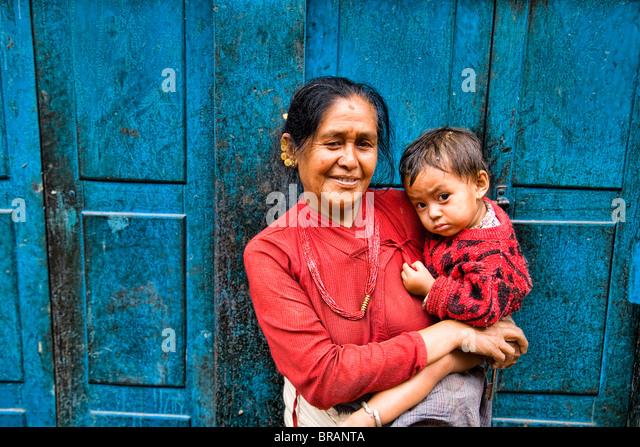 Donna locale con grand bambino nelle braccia nel villaggio di Bhaktapur una città vicino a Kathmandu in Nepal Immagini Stock