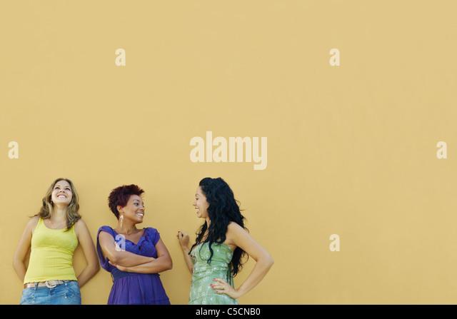 Un gruppo di tre donne amici ispanica appoggiata sulla parete gialla e ridere. Sagoma orizzontale, vita, spazio Immagini Stock