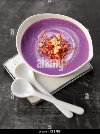 Crema di Vitelotte zuppa di patate con nocciole frantumate e fiocchi di carne dei Grigioni Immagini Stock