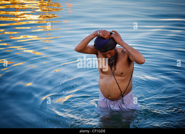 Un uomo Sikh prende un bagno in Amrit Sarovar, la piscina che circonda il tempio d'oro di Amritsar Punjab, India Immagini Stock