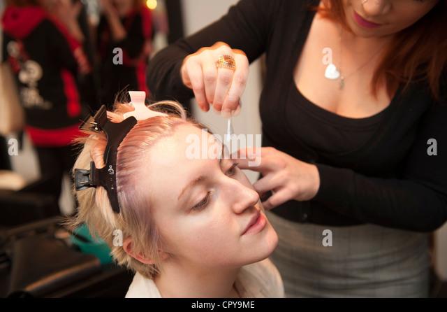Una giovane donna avente un capello e make up bellezza make-over in un salone, sbianca le sopraciglia, REGNO UNITO Immagini Stock