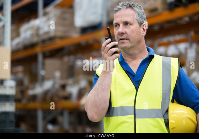 Uomo su walkie talkie in magazzino Immagini Stock