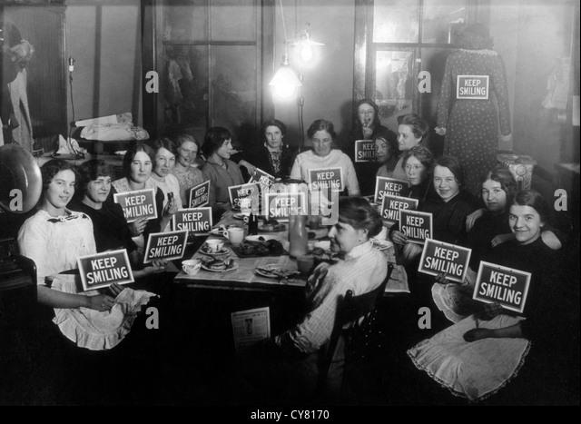 Seamstresses sulla pausa pranzo, tenendo continuare a sorridere segni, circa 1914 Immagini Stock
