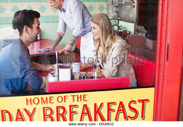 Vista attraverso la finestra del giovane avente un caffè a diner Immagini Stock