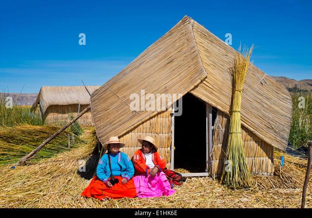 Due donne di Uro indiani indossando vestiti tradizionali seduti davanti ad una capanna di reed, isole galleggianti Immagini Stock