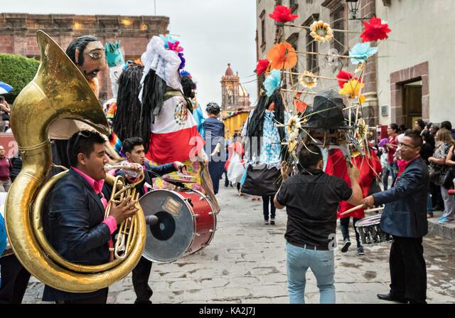 Una Marching Band segue una sfilata di carta gigante-mache marionette chiamato mojigangas in una processione attraverso Immagini Stock