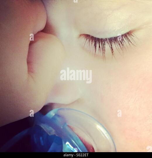 Close-up di un bambino che dorme con un manichino blu succhietto nella sua bocca. Immagini Stock