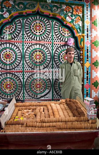 Boy vende biscoitos fora da mesquita Hassan mercado entre muçulmanos, Paquistão Imagens de Stock